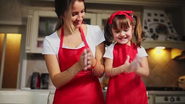 glückliche Familie in der Küche Mutter und Tochter in der Küche spielen mit Mehl, um Spaß zu haben und die Pasteten in der Küche in den gleichen roten Schürzen formen. Stedicam