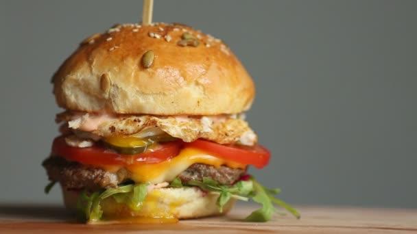 Velký Burger s hovězí kotleta, rajčaty, žampiony a okurky s rozpečeným sýrem se otočí na dřevěné desce na světlé pozadí