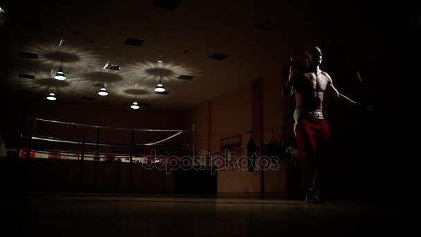 Pugile di formazione cardio sul ring. Saltare la corda