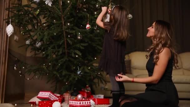 Mutter und Tochter dress up einen Weihnachtsbaum am Heiligabend