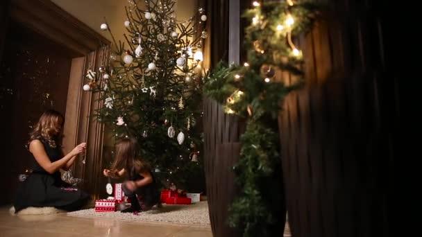 Mutter und Mädchen verkleiden sich den Weihnachtsbaum zusammen