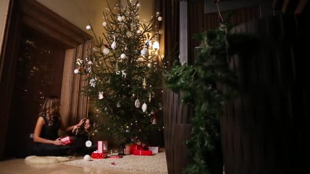 Mutter und Tochter dress up den Weihnachtsbaum. Das Mädchen wählt Weihnachten Spielzeug