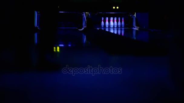 Vítězství v bowlingu. Hráč hází míč na poslední pin a hity. Stroj shromažďuje padlé kolíky a vloží nové.