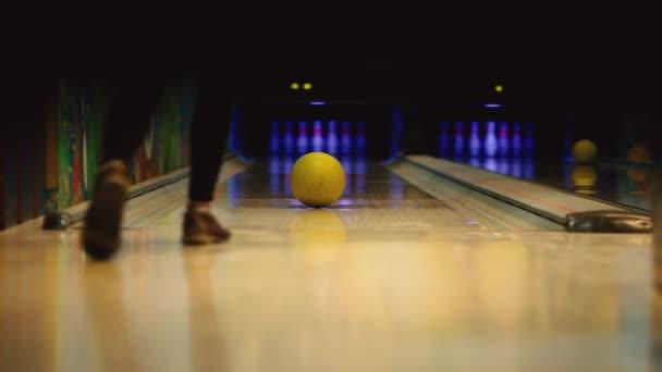 V herní klub pro bowling hráč hodí bowlingovou kouli, která srazí kuželky. Plynulý pohyb těžiště, zepředu dozadu. Hráč omráčil stávky a nohy tančit