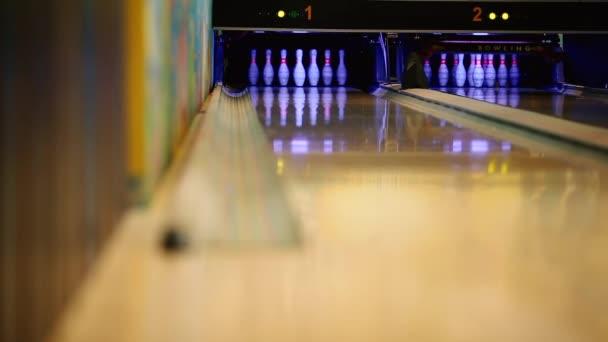 V herní klub pro bowling hráč hodí bowlingovou kouli, která srazí kuželky. Detail, jen vzít pár kolíků