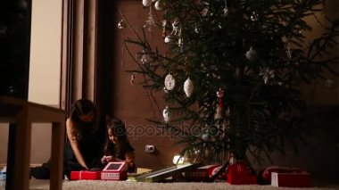 Mom and her daughter unleash the Christmas gift ribbons under the tree in the living room of their house