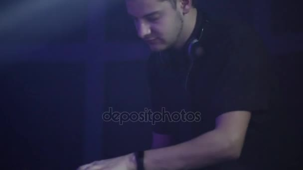 A professional DJ plays musical compositions for people dancing in the club. Musical equipment. Moution camera