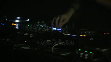 Professional DJ works close-up on the soundbar at a nightclub party.