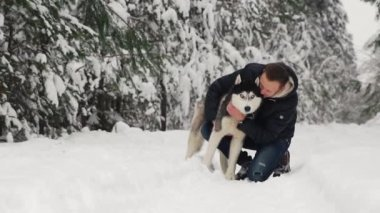 A man hugs his Siberian husky in the forest. In the background trees in the snow. Pride and happiness in the eyes. Walk with the dog.