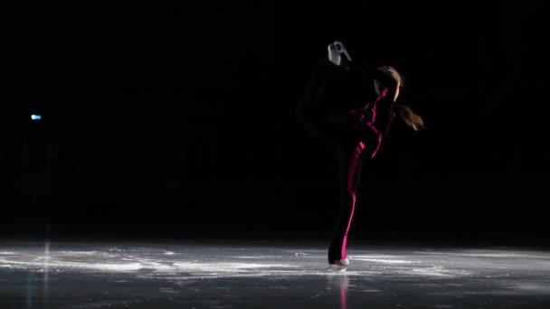 Malá dívka bruslař v černé sportovní oblek a bílé brusle provádí Rotující stojan v aréně zimního stadionu. Noha je zvedl nad hlavu a ruce drží brusle.