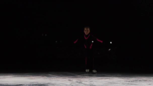 dívka bruslař jezdí do rámečku na bruslích a podívá přímo do kamery. Kamera na pera přesune spolu s ní během cestování. Podsvícení v ice Areně.
