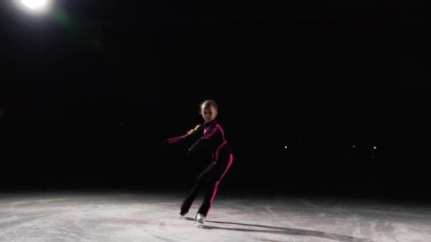 Szakmai lány korcsolyázó mozog körbe helyzetben korcsolyát a jégen, ha a láb van az oldalán, és a kamera is vele együtt mozog. Késleltetett, lövés, szakmai korcsolyázás. Háttérvilágítás