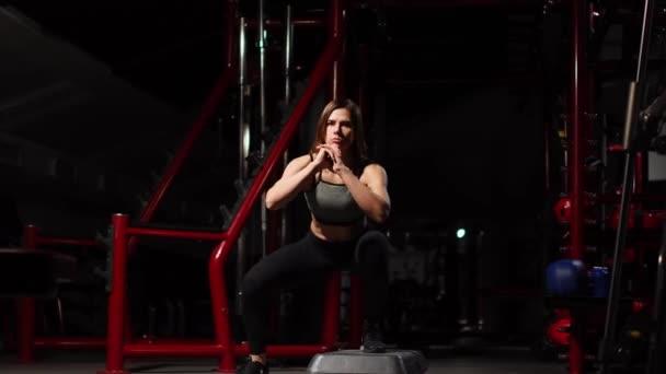 Krok fitness, trénink, aerobik, sportovní koncept - trenér atletické žena na krok dělá aerobní s šlapadla uvnitř. Fitness žena s platformou krok dělá cvičení