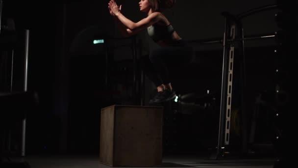 Krásné ženské fitness atlet provádí box skoky v temné tělocvičně černém sportovní a krátké legíny s tváří skryté