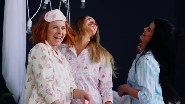 Női pizsama party, három gyönyörű és szexi lány nevetni és táncolni az ágyon.