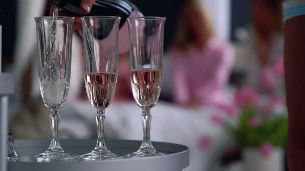 Nahaufnahme eines schönen Mädchens füllt sich mit Champagner-Gläser für Freundinnen, die im Hintergrund auf einer Bachelorette Party amüsieren. Pyjama-Party mit Alkohol