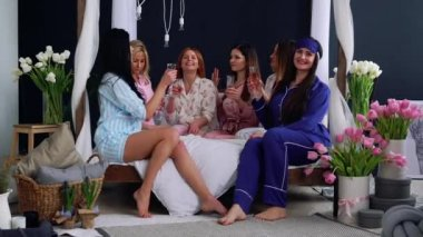 A group of young and beautiful girls in pajamas sitting on the bed with glasses of champagne and celebrate her friends bachelorette party smiling and having fun at a wedding party. Lifestyle luxury.