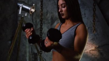 Sexy sporty girl in short shorts and inflated press with dumbbells indoors on the background of a stone gray wall raises her hands with dumbbells for bicep training. Close up. Simultaneous lifting of