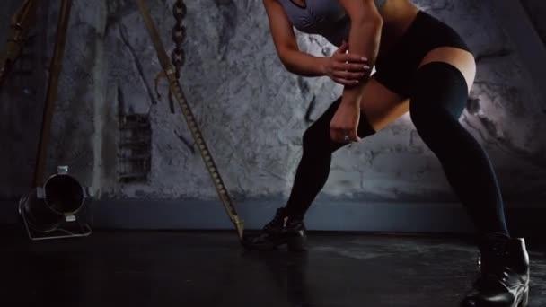 Brutális sport lány csinál a zömök, egyik lábát, a zuhatag. Alsólábszár- és combsúlyokat edzés közelről. A fitness tréning. A koncepció egy erős edzés