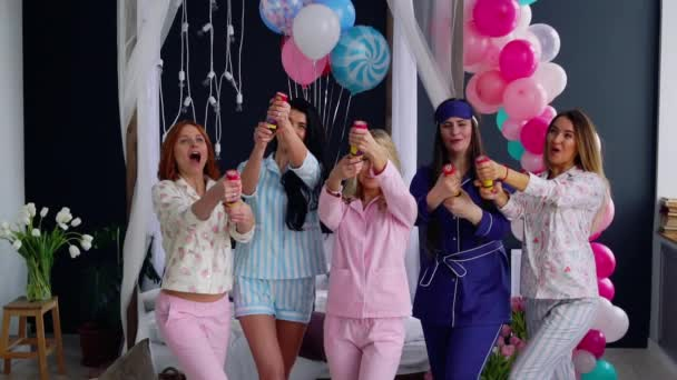 A group of girls laughing and smiling in pajamas launching confetti in slow motion 120 frames per second.
