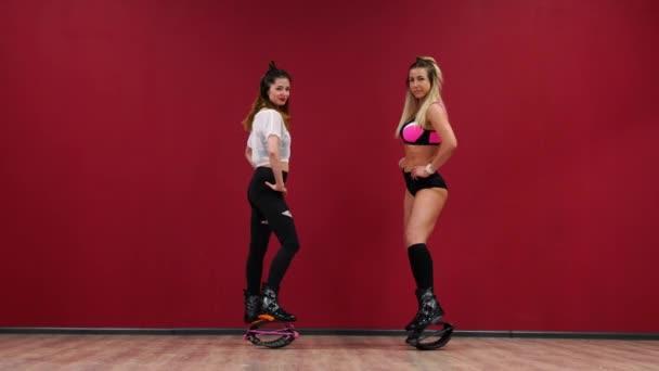 Krásné sexy dívky na červeném pozadí zdi dělá fitness cvičení na speciální boty kango skok