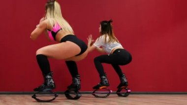 A beautiful sexy girl on a red wall background performs squats to strengthen the thigh muscles. Training of gluteal muscles in boots on springs. Sports shoes Kangoo Jumps