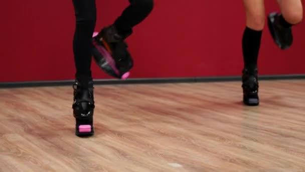 Krásné sexy dívky na červeném pozadí zdí provést fitness cvičení na boty s pružinou. Kardio trénink ve stylu skoku. Přechod bez zastavení. Spalování tuku a sternafia postava s