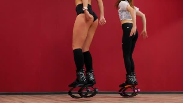 Krásné sexy dívky na pozadí červené zdi provádí dřepy posilovat stehenní svaly. Školení hýžďové svaly v botách na prameny. Sportovní boty Kangoo skoky