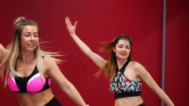Dvě krásné sportovní dívky provádět aktivní spalování tuků cvičení skákání jako klokan v speciální obuv. Kardio cvičení pro vytrvalost. Kango skok