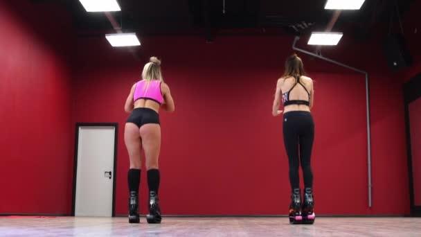 Krásné sexy dívky na pozadí červené zdi provádět běh cvičení v tělocvičně v jarní kabáty. Veselá školení s kango skok Zpomalený pohyb