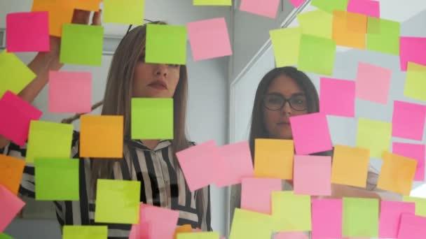 Kreativní podnikání tým diskuzí spolupráce sdílení dat pozdě v noci po hodinách v kanceláři moderního skla. Dvě velmi krásné dívky v úřadu oblečení blondýnka a brunetka s brýlemi