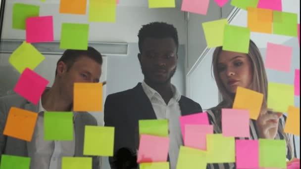 Kreativní podnikání tým diskuzí spolupráce sdílení dat pozdě v noci po hodinách v kanceláři moderního skla. Multi etnické tvůrčí tým provádí všechny jejich nápady jsou vloženy debaty