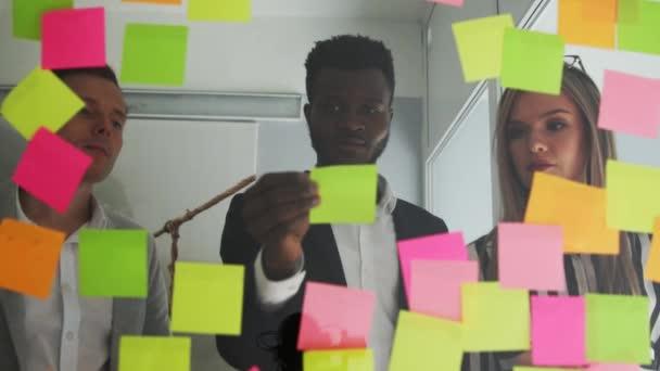 Multi etnické tvůrčí tým vede debata, kterou všechny jejich nápady jsou vloženy na barevné samolepky na zeď sklo. Američan Afričana muž a blondýna tým se v kanceláři