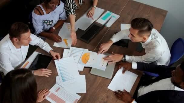Blick von oben auf den großen Schreibtisch, hinter dem das Büro-Team aus kreativen Managern unterschiedlicher Nationalitäten Brainstorming macht. Aufstieg und Fall des Kryptowährungsmarktes