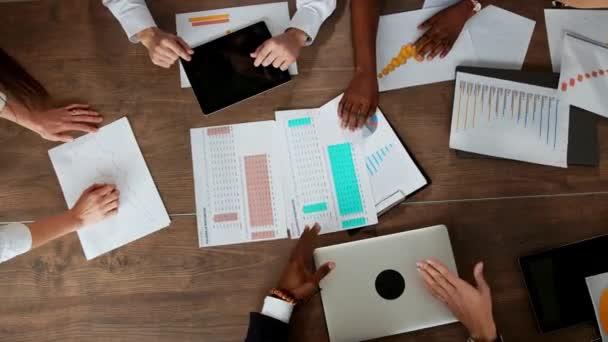 Pohled shora na velký stůl, za nímž úřad tým kreativních manažerů různých národností je debata. Vzestup a pád trhu kryptoměn