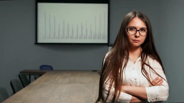 Portrét krásné dívky, v kanceláři oblečení stojící v konferenční místnosti s brýlemi při pohledu na fotoaparát