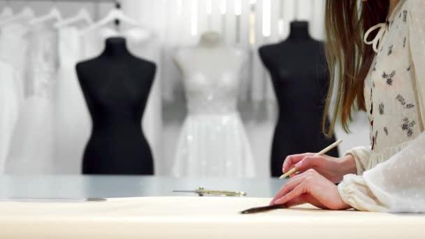 Krásná dívka módní návrhář nakreslí na papírové šablony k vyřezávání tkaniny na figuríny oblečené do svatebních šatů. Výrobce svatebních šatů.