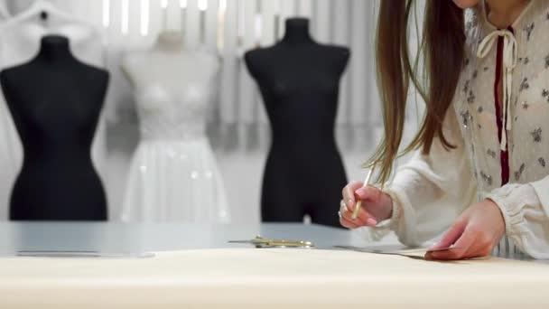 Krásné módní návrhářka dívka vystřihnout na papíře s zlaté nůžky vzory pro tkaniny na pozadí figuríny oblečené ve svatebních šatech. Výrobce svatebních šatů.