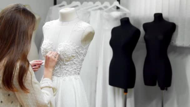Portré egy lány, egy esküvői ruha, exkluzív megrendelés varrás szövet és strasszokkal létrehozása egy ruha, egy manöken öltözött. esküvői ruhák gyártása. Kis üzlet