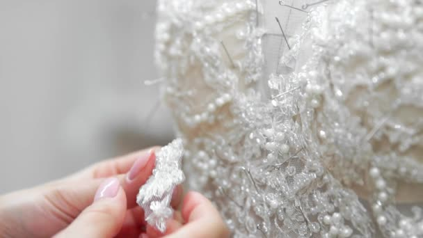 Close-up-Mode-Designer für Bräute in seinem Atelier pins Nadeln Hochzeit Spitzenkleid. Schneiderin schafft eine exklusive Hochzeitskleid. Sichern Sie mit Nadeln Umriss. Kleine private Unternehmen. Nähen