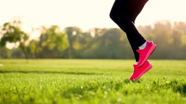 Při západu slunce v oblasti sportovní dívka na trávě v bílé horní a růžové tenisky díky warm-up běhu před zrušením boky. Sport. zblízka. Trávy boty