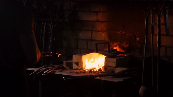 Hardening of the metal by sharp cooling in water. There is steam. The blacksmith tempers a red-hot sword on an old technology. Creation of ancient weapons. Blacksmiths Armory.