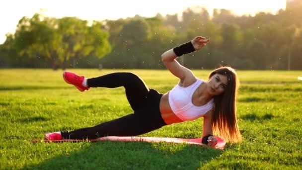 Žena, která dělá cvičení břicha drtí na fitness mat v letním parku v pomalém pohybu při západu slunce.