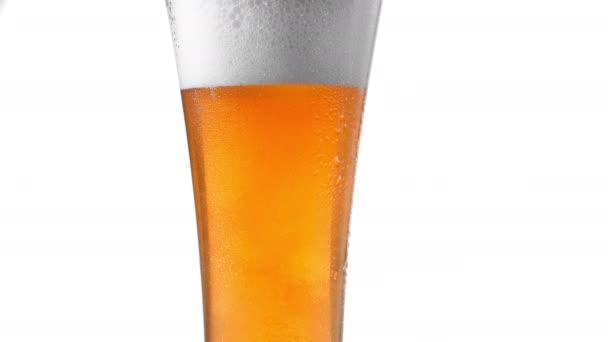 Close up pozadí bílá s bublinami pivo ve skle, nízký úhel pohledu, zpomalený pohyb.