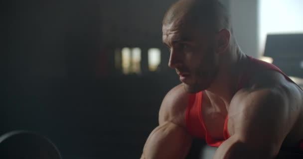 Síla tréninkové rameno biceps s činkou. Slim silný muž s velkými svaly zvedne činku sedí v tělocvičně na lavičce