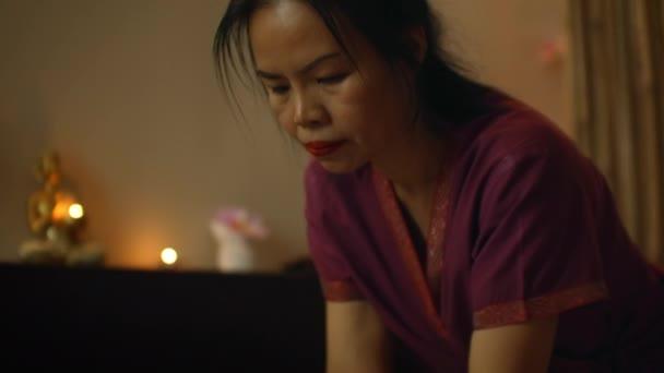 Thajská masérka masíruje ženy v lázeňském salonu. Asijská krásná žena dostává thajské bylinné masáže kompresní masáž v lázních. Krása thajské masáže koncept