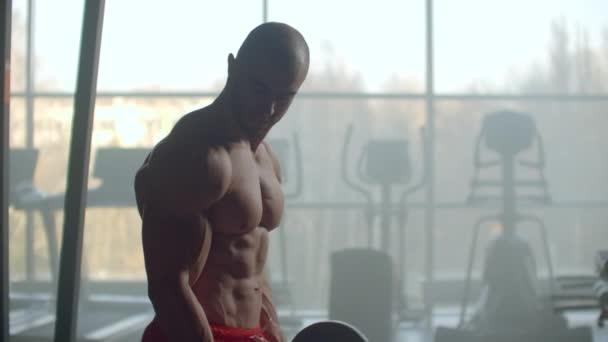 Muž bez košile zvedne činku s činkami na bicepsy. Výcvik silných rukou ve zpomaleném filmu proti velkému oknu v moderním stylovém fitness centru.