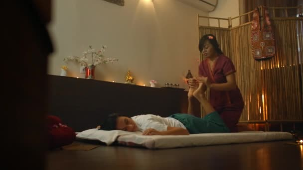 junge Frau im Liegen, während sie die Akupressur-Techniken der traditionellen Thai-Massage im luxuriösen Spa- und Wellnesszentrum genießt.