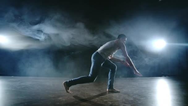 A férfi táncos egy kaszkadőr ugrást hajt végre, egy visszafordulással és egy forradalommal a füstben a reflektorfényben. Modern balett.