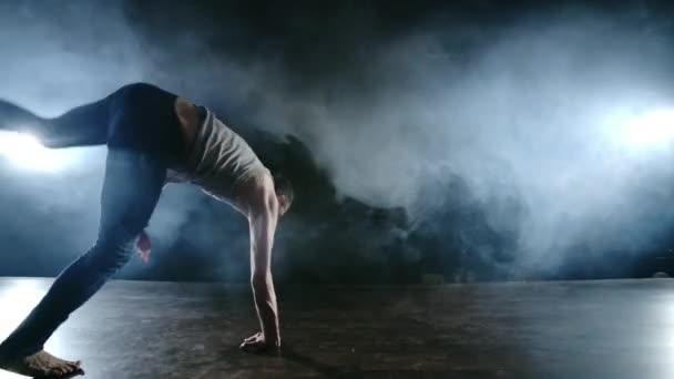 Modern balett, egy férfi ülő helyzetből a színpadon hátraugrik forgatással a sötét színpadon a füstben a reflektorfényben